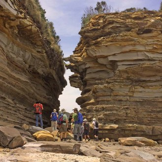 Walkers moving through the rock formation
