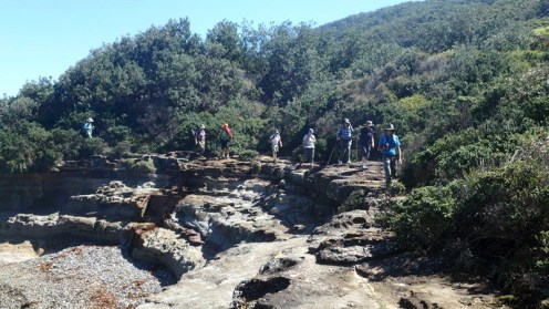 The group emerging from the forest onto the rock platform approaching Pretty Beach.