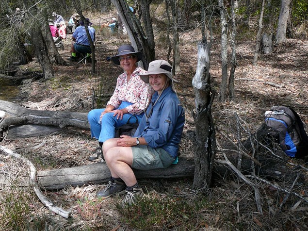 Karen and Helen on a comfy log by the lake.