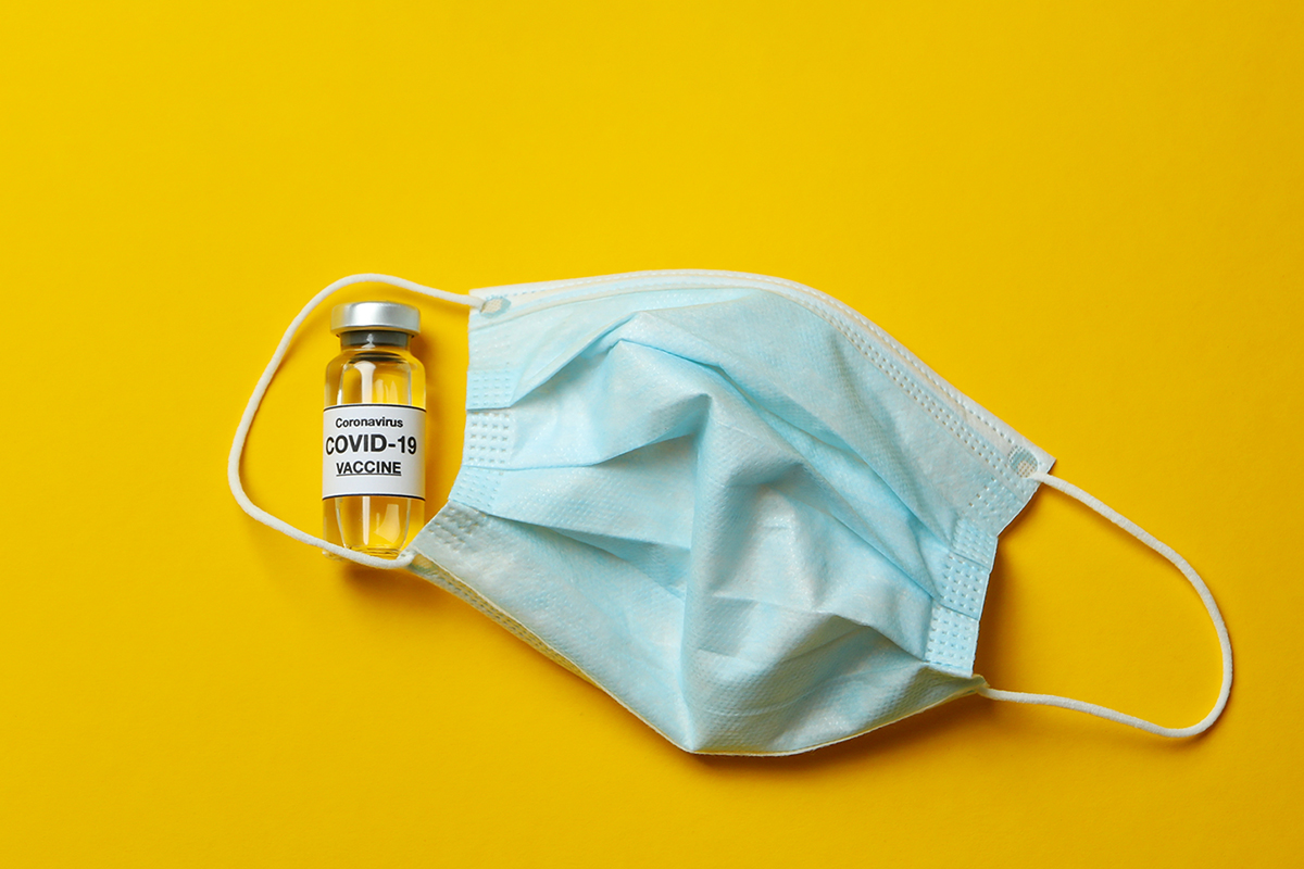Vial of Covid - 19 vaccine and mask on yellow background