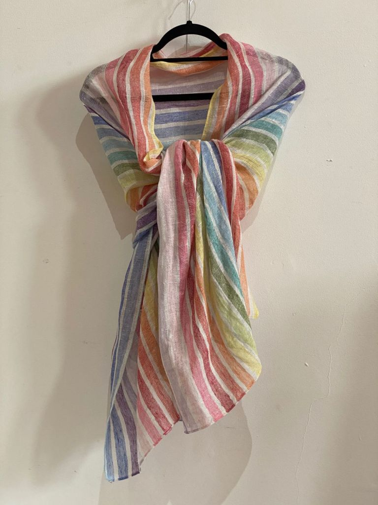 a rainbow coloured linen scarf knotted around a hanger, hanging against a white wall