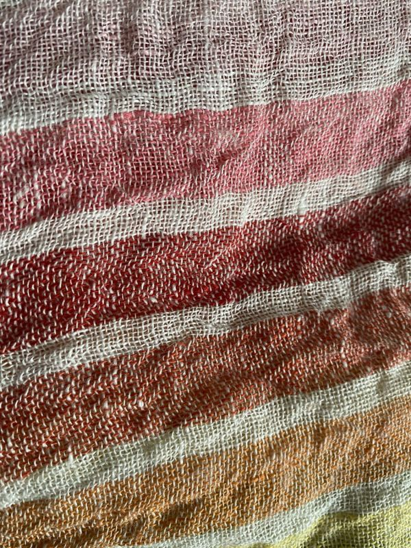 close up of yarn-dyed linen cloth, showing the different colours of warp and weft