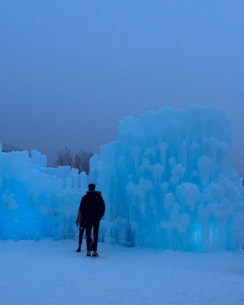 Couple stands outside the Ice Castles