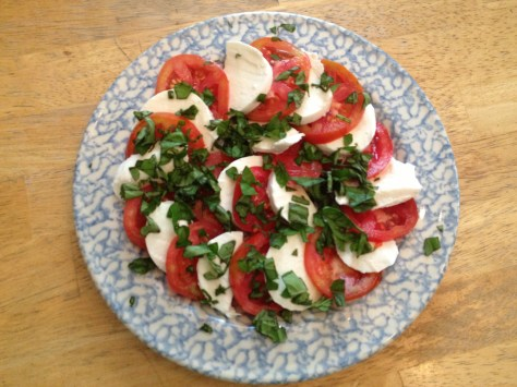 photo of tomatoes and mozzarella sliced and arranged on serving plate sprinkled with chopped basil