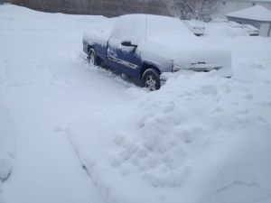 Photo of blue pick-up truck covered with snow