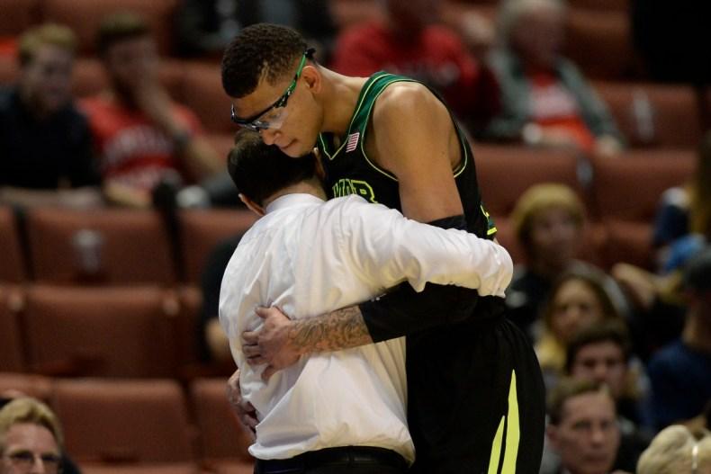 Исаии Остин обнимает своего тренера, после того, как его сняли с матча по состоянию здоровья