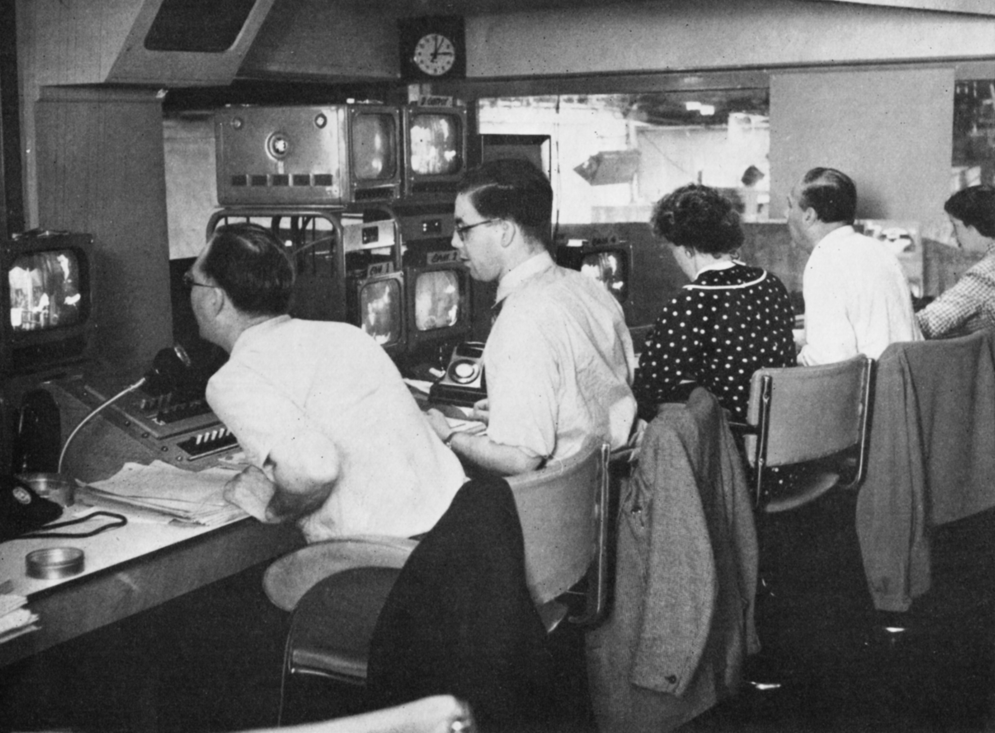 Three men and two women at a control desk covered in monitors.
