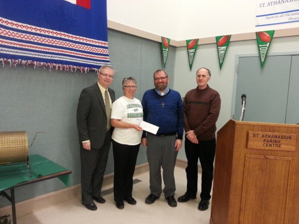 Andrij Lazurko presenting the 2016 Eparchial Appeal Rebate and Parish Internal Goal cheque to Father Basil Malowany, Rosanne Miller and Terry Shalley from St. Athanasius Parish in Regina.