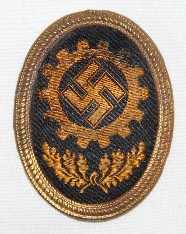 P016. WWII GERMAN DAF VISOR CAP BADGE