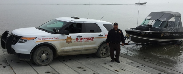 VPSO Cpl. Roger Wassillie, Togiak VPSO posing with his USDOJ COPS VPSO equipment used for SAR(Search and Rescue), Fire, EMS and Law Enforcement use while on duty.