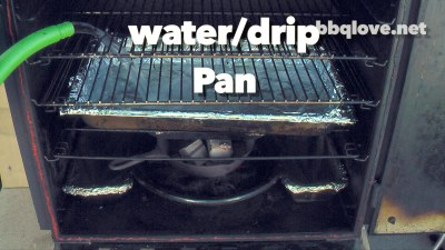 Adding water to the water pan/ drip pan in the vertical water smoker. Front View