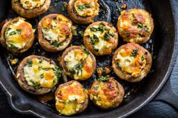 Baked mushroom poppers filled with cheese, parsley, and roasted garlic in black dish