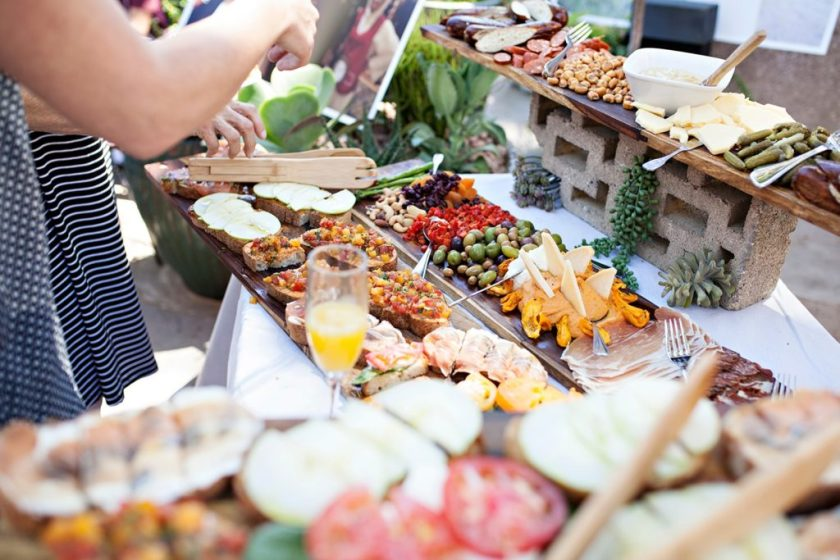 Buffet table outdoors filled with various foods that could be eaten as sides at a barbecue party