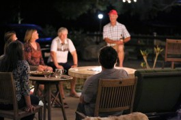 Group of middle-age friends and family sitting around a firepit eating food and playing games