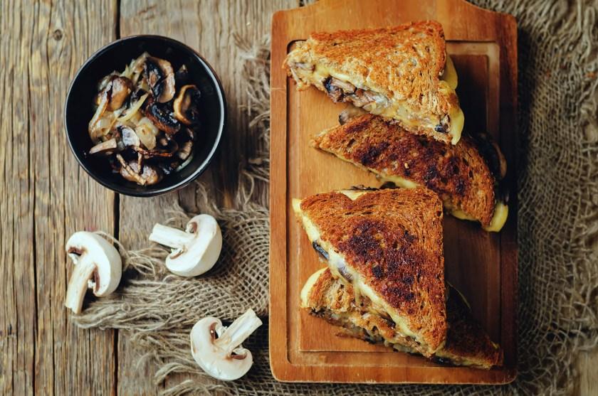 Mushroom Grilled cheese sandwich on rye bread sitting on top of wooden board