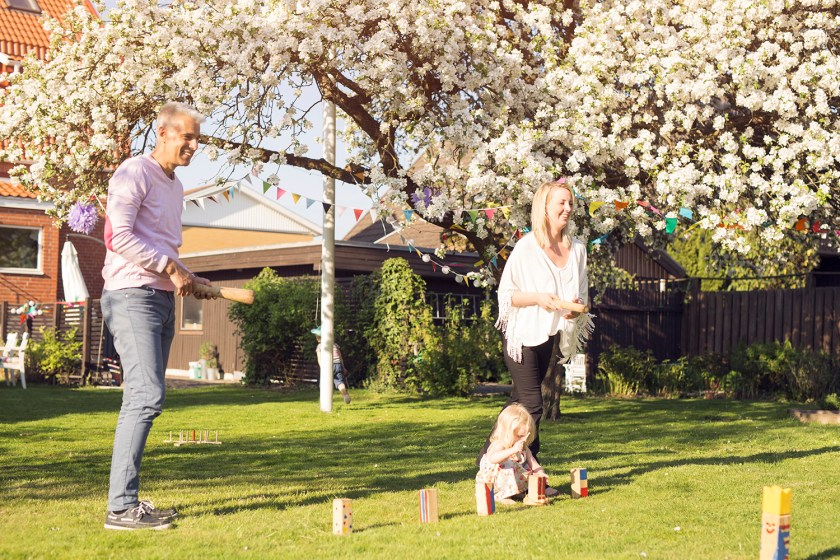 Little girl squatting down in backyard to play Kubb with her family