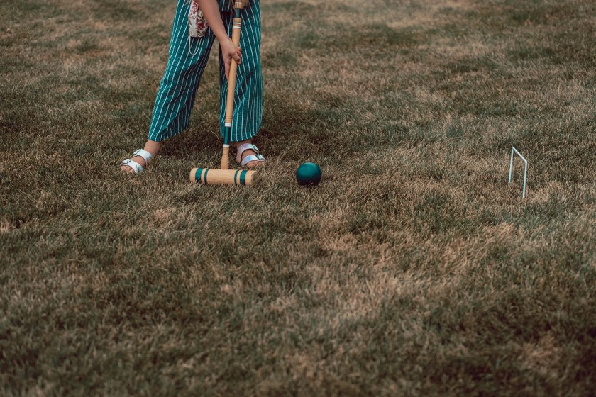 Person playing croquet and holding mallet to strike wooden ball through hoop in backyard