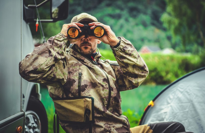 Hunter using binoculars to search for game outside of tent and truck