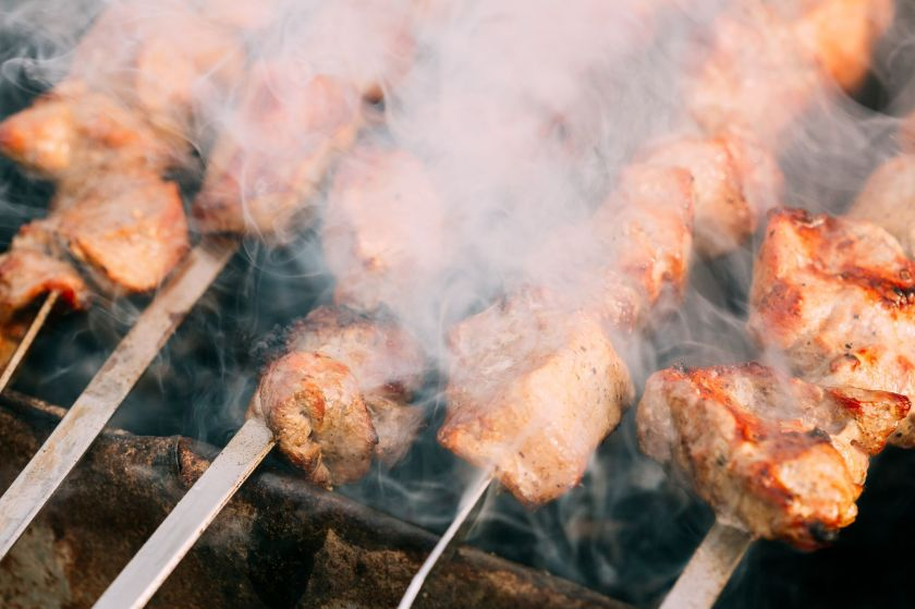Close up of pork kebabs smoking on a grill.