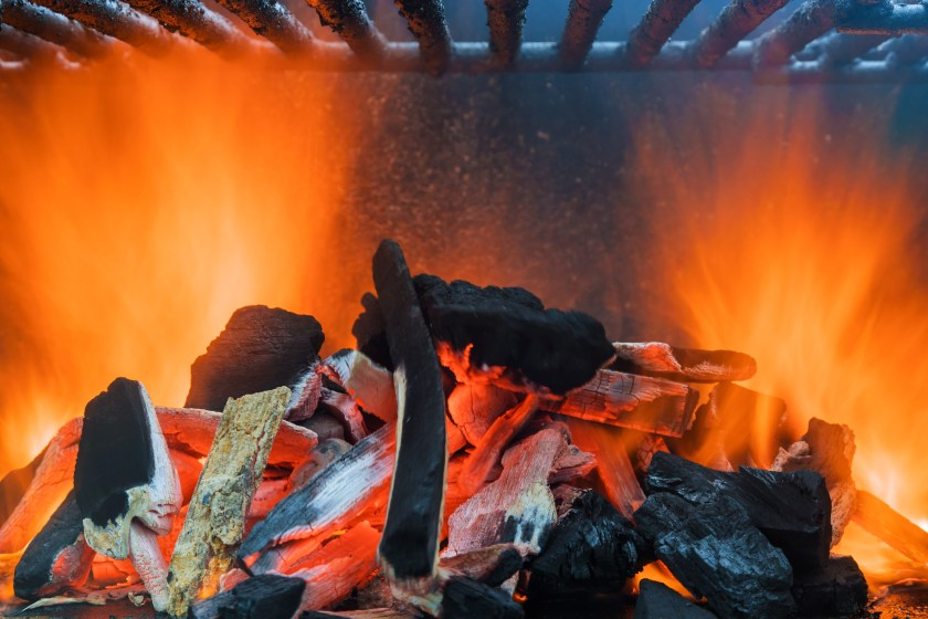Charcoal and wood pushed over to one side of the grill and under the grates and on fire.