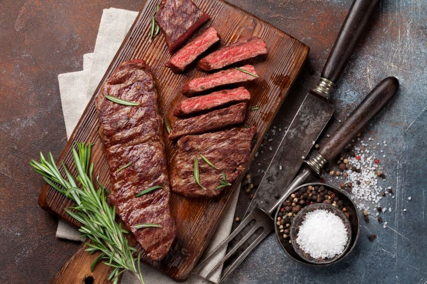 A top blade or denver steak cut into pieces on a wooden board with a cutting blade and fork and seasoning on the surface nearby.