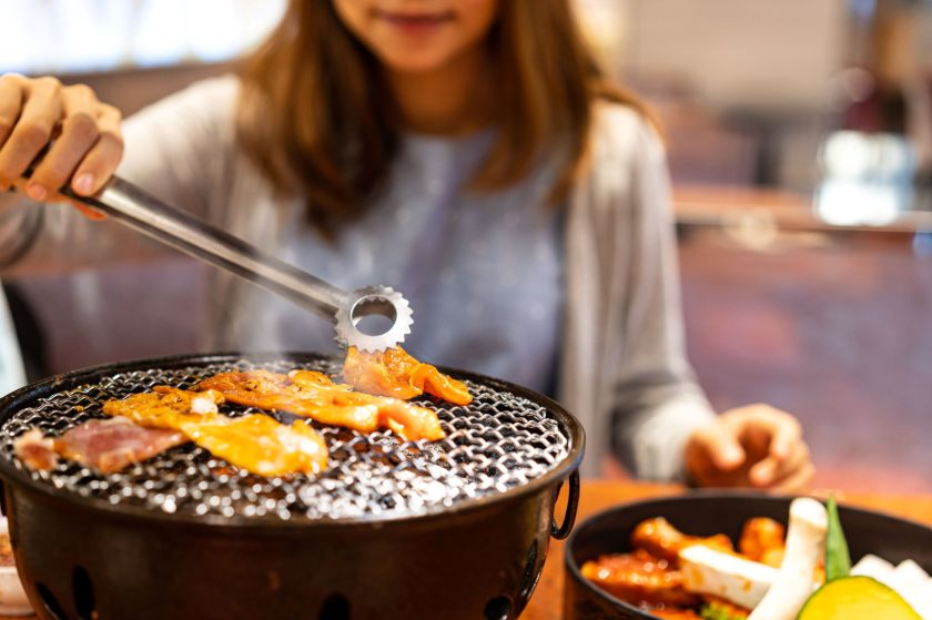 Woman cooking korean barbecue over a hibachi grill at a restaurant