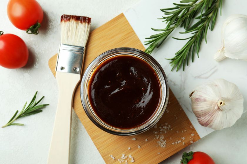 Sauce in a cup on a wooden board with a brush next to it and the end covered in some of the sauce.