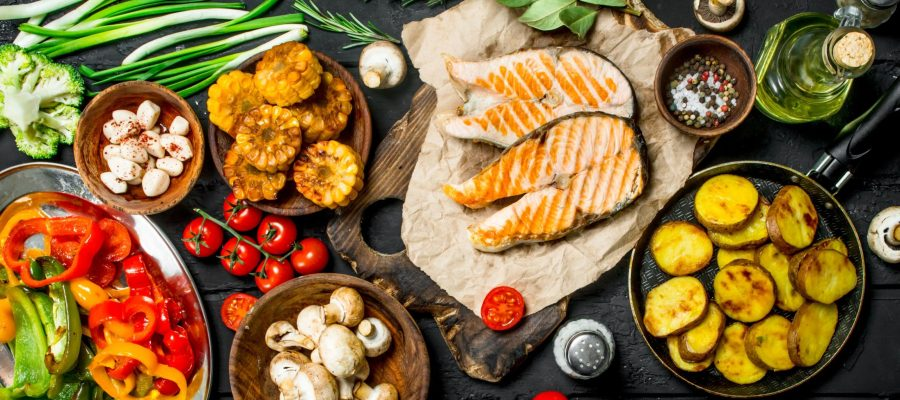An assortment of different grilled healthy foods like salmon and vegetables like corn.