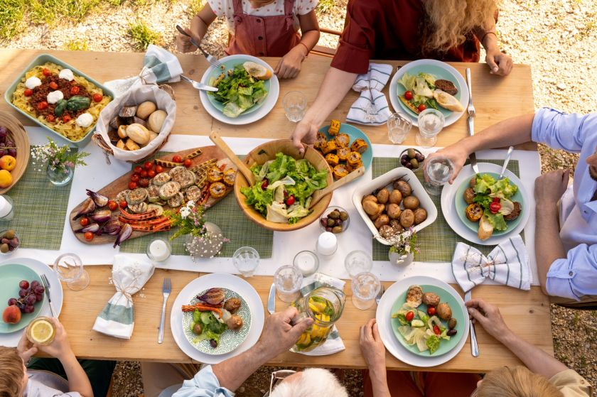 People sitting around a wooden table eating food outside and are passing a bowl of salad around.