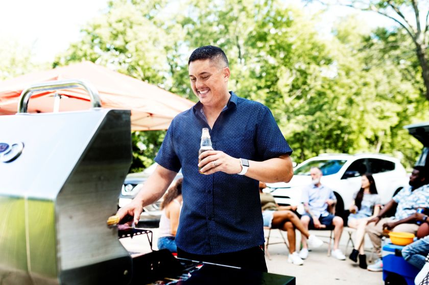 Man standing at a grill outside near cars with his friends behind him as they tailgate and he cooks food.
