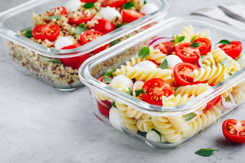 Two food safe containers to store food in that have pasta salad and other fresh veggies and oats and pasta in them.
