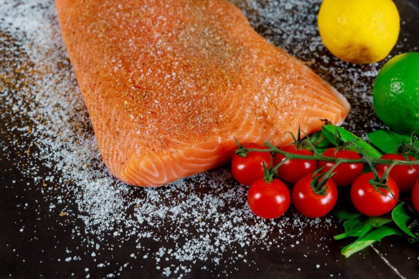 Salmon covered in a spice blend on a black surface next to some tomatoes and other fresh produce.
