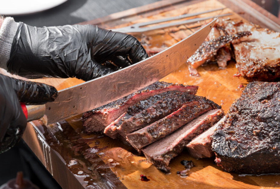 Slicing A Portion Of Roast Beef Brisket With A Large Knife