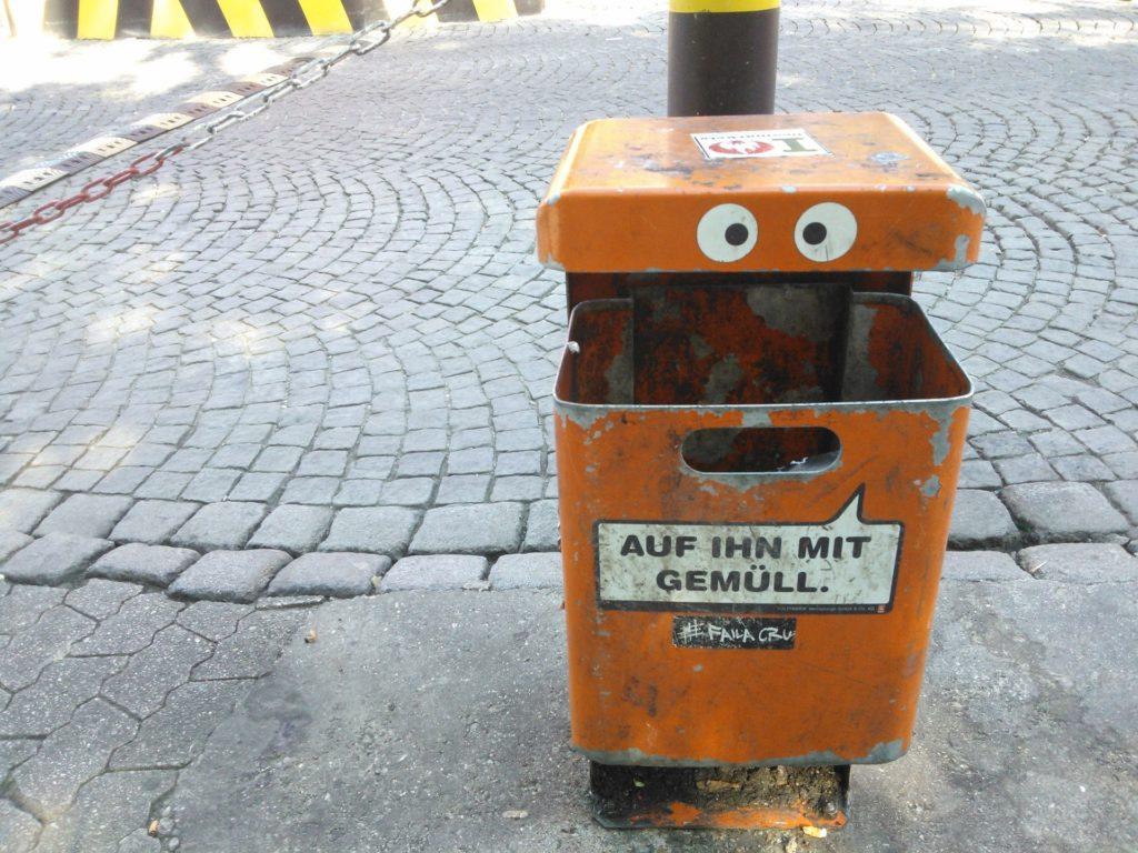 """Abfalleimer in der Stadt mit aufgeklebten Augen und der Aufschrift """"Auf ihn mit Gemüll""""."""