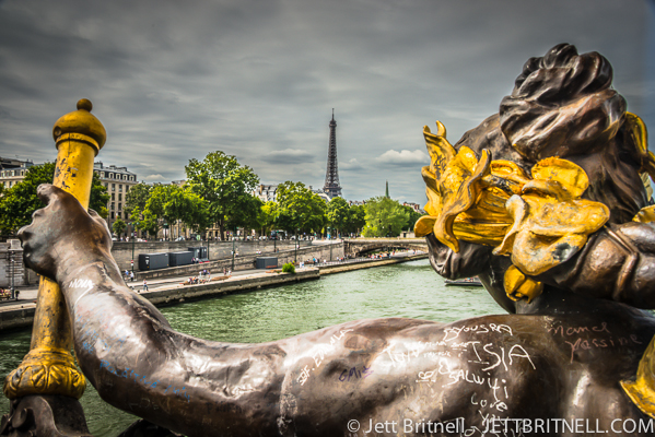 Small statue of a cherub on the Pont Alexandre III with Eiffel Tower in background in Paris