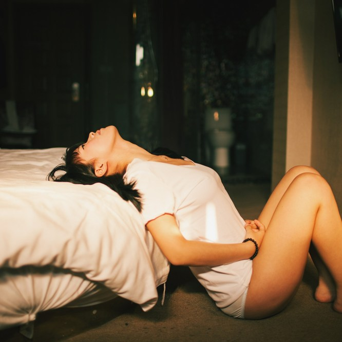Woman sitting at the end of a bed