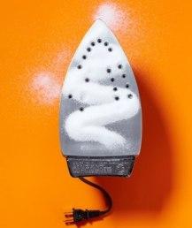 Удалите пятна накипи с утюга, прогладив им лист бумаги с рассыпанной по нему солью.