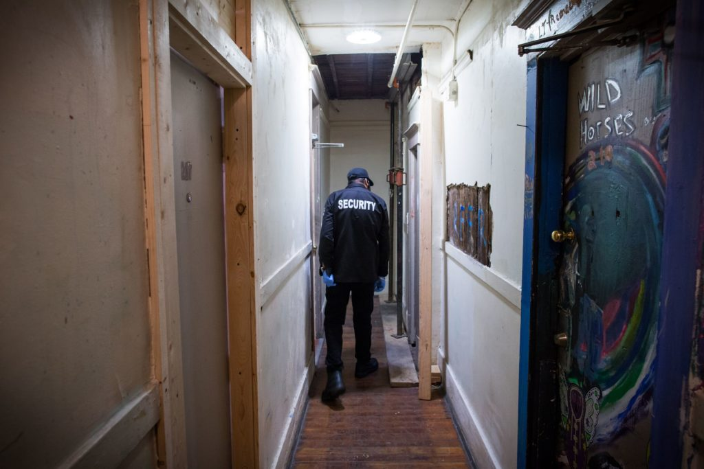 A security guard checks the run-down shared bathroom at the Sahota-owned Regent Hotel. DARRYL DYCK/THE GLOBE AND MAIL
