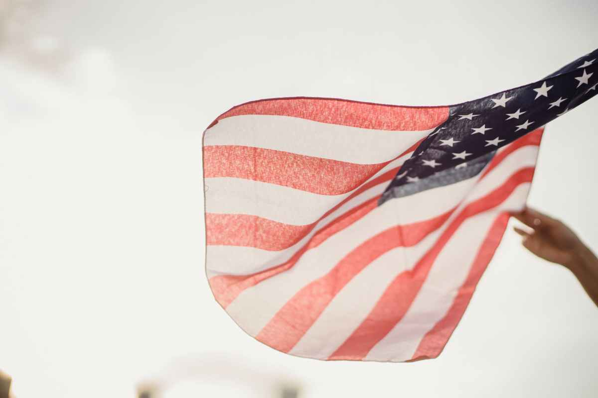 crop person holding american flag against sky