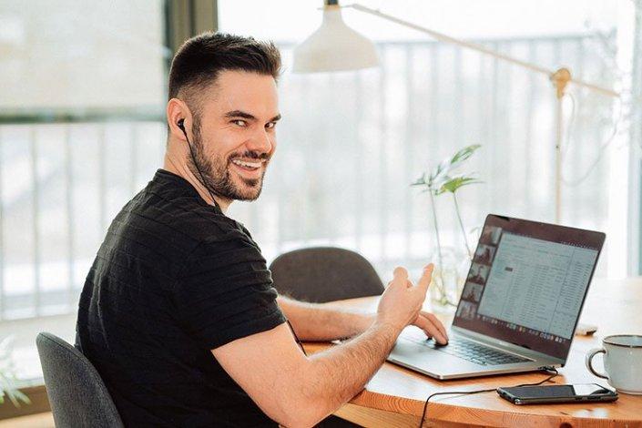 Mann sitzt lächelnd am Tisch vor seinem Laptop in einer Online-Besprechung und deutet auf den Bildschirm