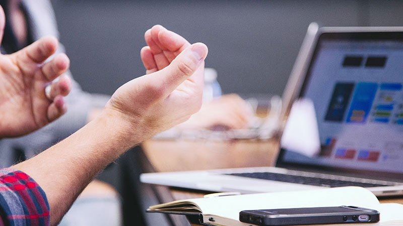 Männliche Hände mit erklärender Geste vor einem Laptop