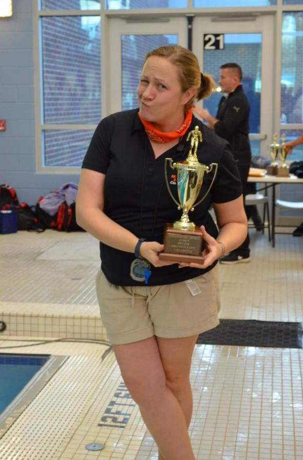 Swim+coach+Mrs.+Livengood+poses+with+their+trophy+after+a+successful+meet.+