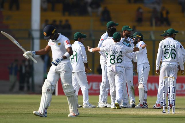 Pakistan`s cricketers celebrate after the dismissal of Sri Lanka`s Dinesh Chandimal (L) during the second day of the second Test cricket match between Pakistan and Sri Lanka at the National Cricket Stadium in Karachi on 20 December 2019. Photo: AFP