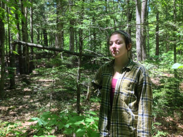 Rachel Borch, 21, stands in the woods near her home in Hope. Borch was attacked while on a jog in woods near her home by a rabid raccoon and had to drown the animal in self defense.