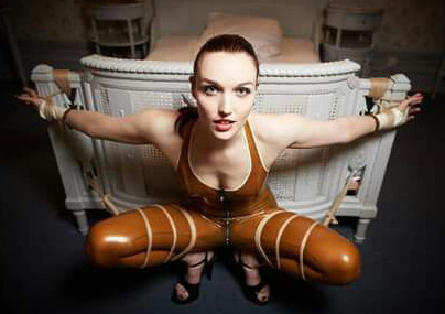 The Dutch Dame en tenue de latex marron, encordée à un lit