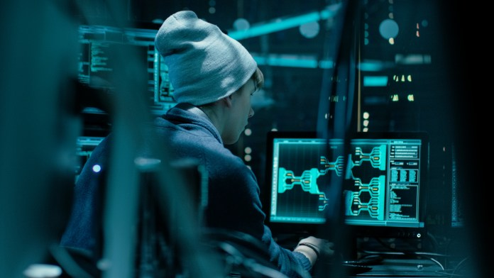 Back View of Teenage Hacker Working in Computer and Infecting wi