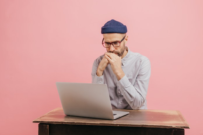 Horizontal shot of concentrated male worker reads statistics attentively, focused in laptop computer, learns something online, wears spectacles, hat and white shirt, isolated over pink wall.