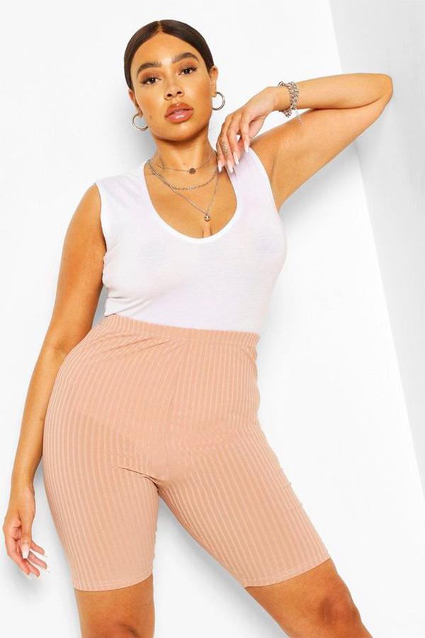 A plus-size model wearing peach bike shorts.
