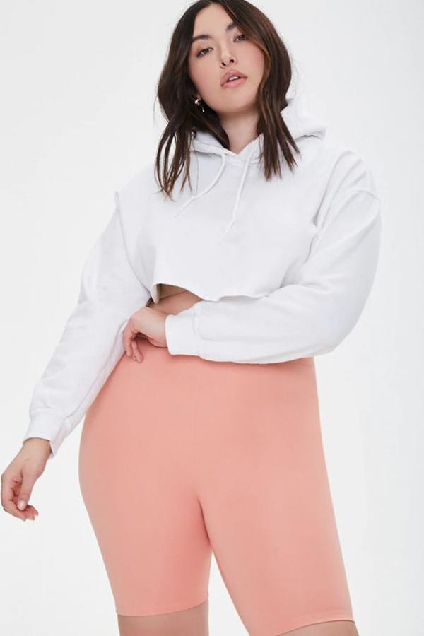 A plus-size model wearing light pink bike shorts.