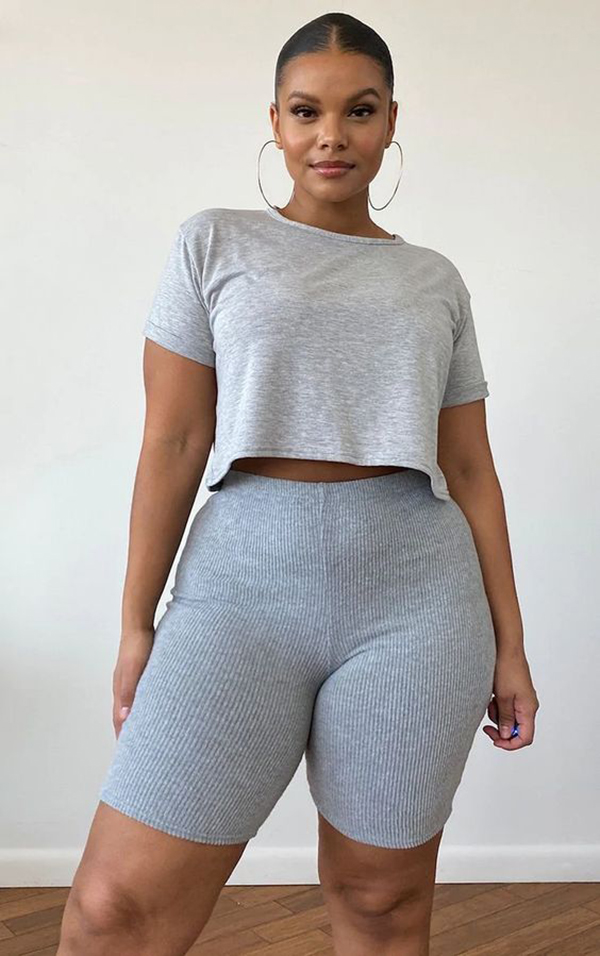 A plus-size model wearing gray bike shorts.